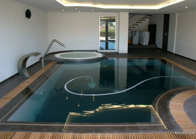 Piscina de hormigón, interior, gresite blanco y marrón, desbordante con spa